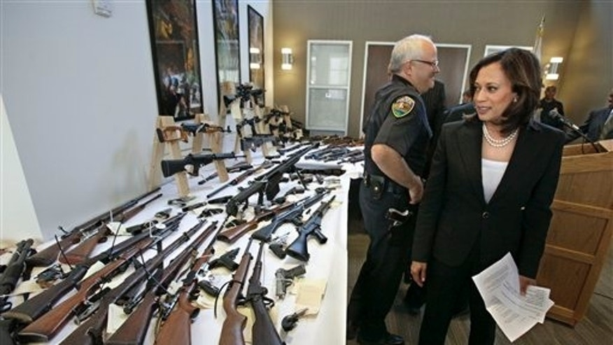 June 16: Attorney General Kamala Harris looks over some of the guns seized from individuals legally barred from possessing them following a news conference in Sacramento, Calif. In a recently concluded six-week sweep conducted by agents from the Department of Justice, 1,200 firearms were seized from individuals barred from owning them,including those determined to be mentally unstable and with active restraining orders against them.
