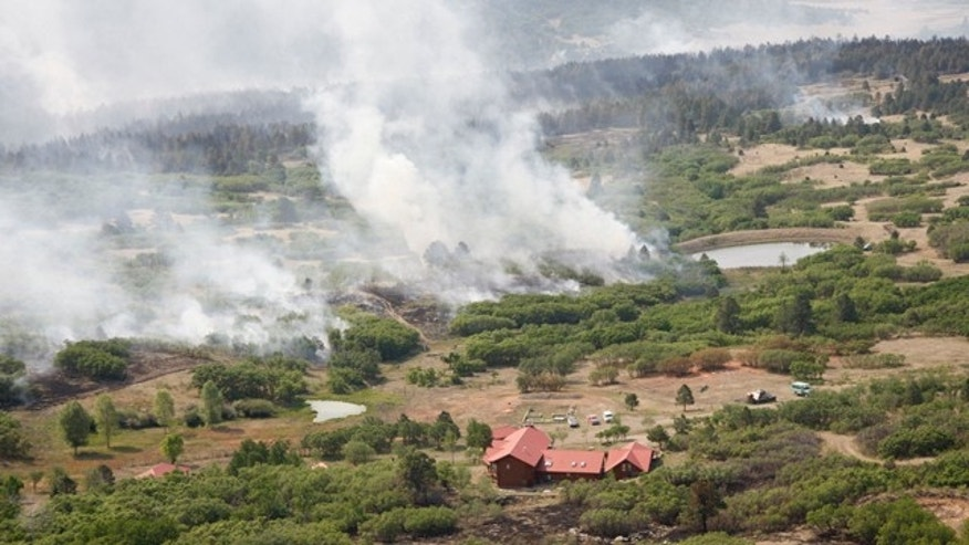 June 16: Smoke billows from the track forest fire near a home north of Raton, N.M., as seen from a KOAT-TV helicopter.