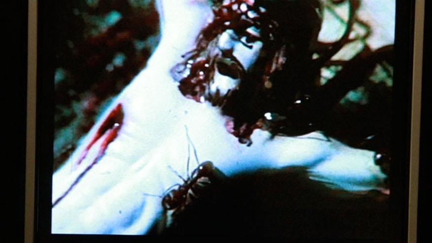 "A crucifix in the video ""A Fire in My Belly,"" part of the 'Hide/Seek' exhibit at the Smithsonian's National Portrait Gallery. The image shows Christ on the cross with ants crawling over his body and face. (CNSNews.com/Penny Starr)"