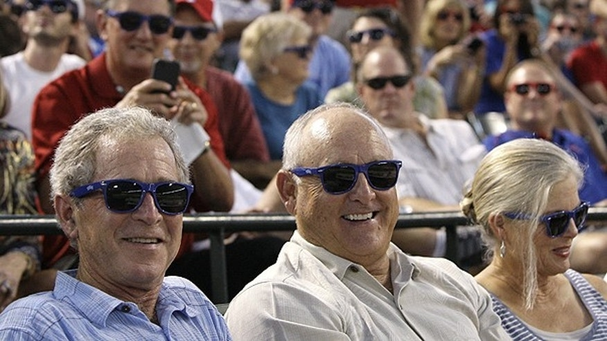 June 21: Former President George W. Bush, from bottom left, Texas Rangers team president Nolan Ryan and Ryan's wife, Ruth, right, put on sunglasses as they take in an interleague baseball game between the Houston Astros and Texas Rangers in Arlington, Texas.