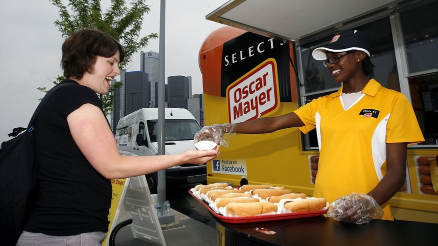 Julie Updyke of Ferndale, Mich., left, receives a complimentary hot dog from Teri Block of Southfield, Mich., as they gather around the first-ever, special edition Wienermobile Food Truck that serves Oscar Mayer Selects Beef Franks on Tuesday, June 21, 2011, in Detroit.