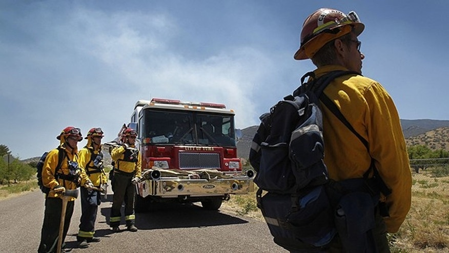 June 21: Capt. Rob Welch, right, and his team from the Yuma Fire Department, prepare to clear fuel in preparation for a back-burn to protect homes in Ramsey Canyon in Sierra Vista, Ariz.
