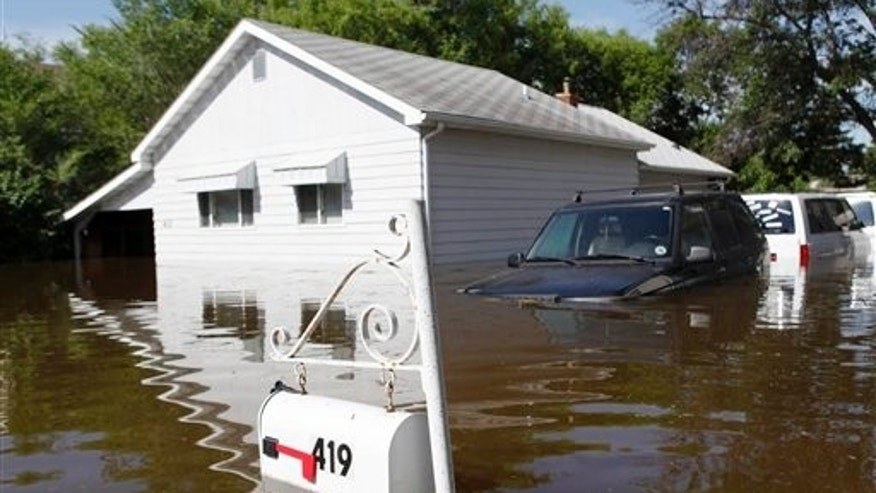 June 25: A home and three vehicles are surrounded by the Souris River flood waters in the Minot, N.D., neighborhood of Oak Park. The Souris River neared its crest Saturday in Minot, where city officials hoped to ride out the high water without losing more than the thousands of homes already damaged by flooding.