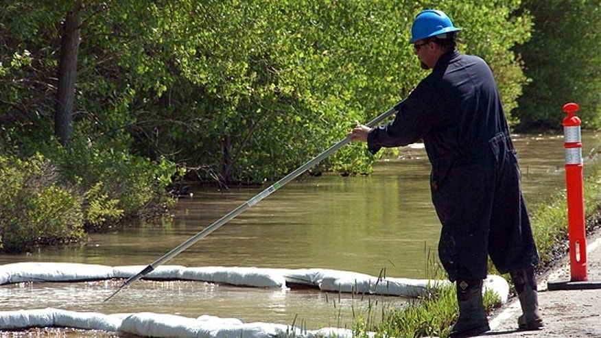 July 2:  A contractor for ExxonMobil tends to an oil containment boom along the Yellowstone River near Laurel, Mont., after a pipeline that runs under the river ruptured. The pipeline break was contained early Saturday morning but the spill stretched over dozens of miles.