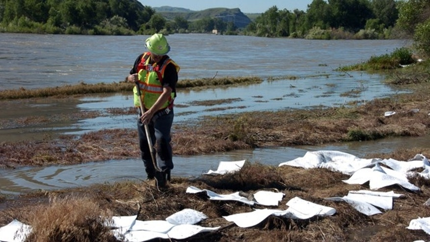 July 3: An ExxonMobil contractor cleans up oil along the banks of the Yellowstone River in Billings, Mont.