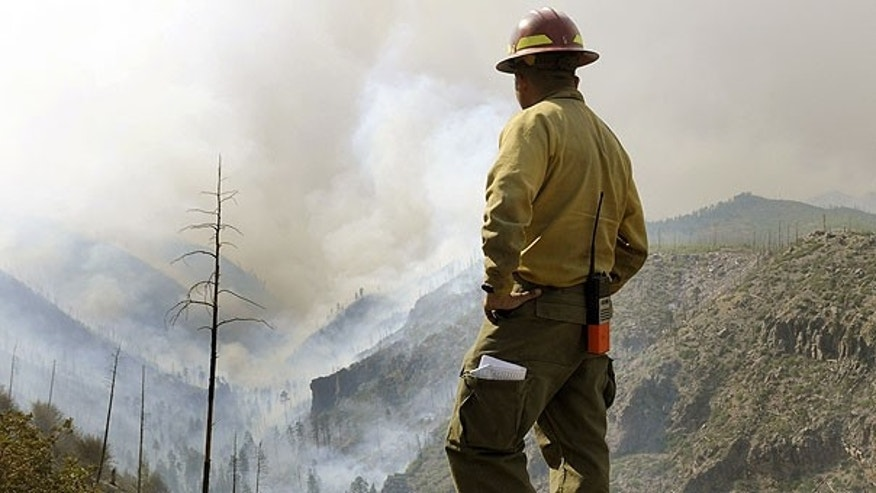 July 1: Firefighter Eugene Pino stands high above a smoke filled Los Alamos Canyon, near Los Alamos, N.M.