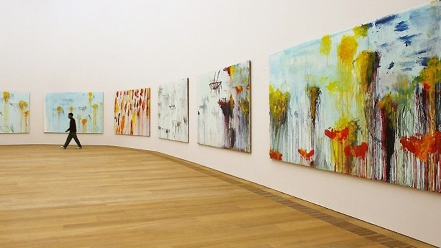 A man walks past the paintings of Cy Twombly in the new Museum Brandhor modern art museum in Munich, Germany.