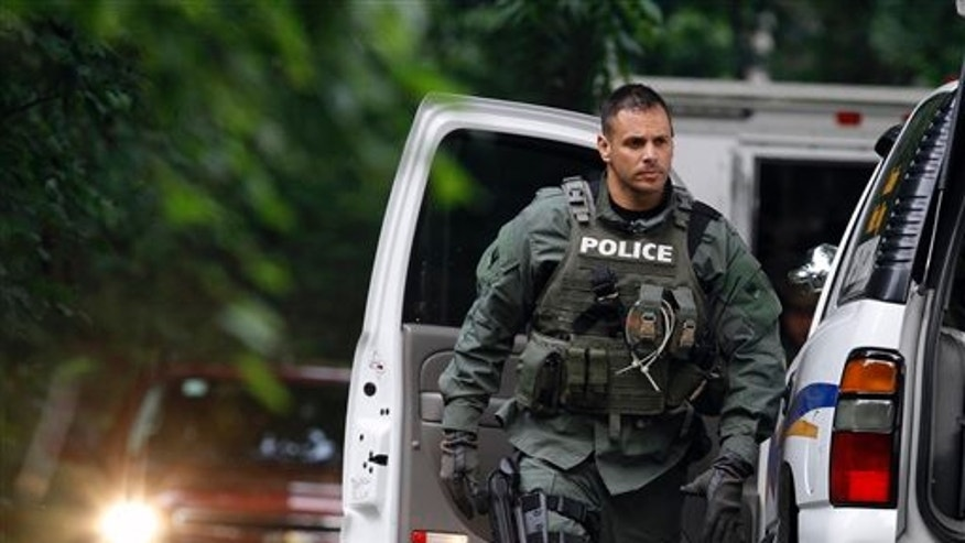 July 3, 2011: A police officer walks near vehicles on Renninger Road in Douglass Township, Pa., as he arrives near the scene of a fatal shooting.