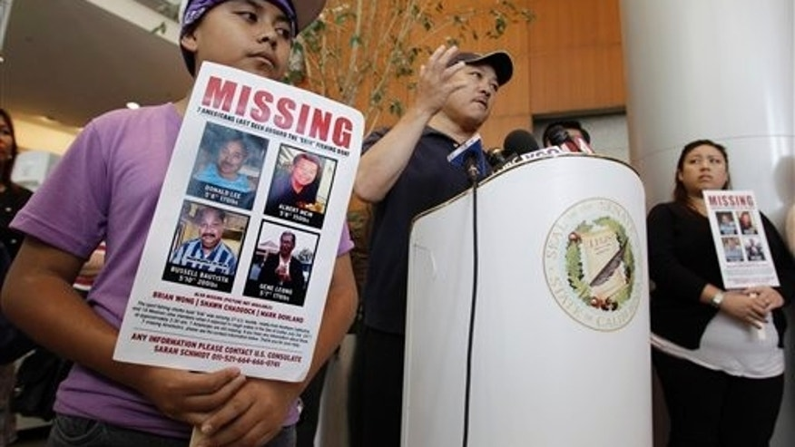 July 6: Matthew Tsujiuchi, 11, holds a sign for his friend and missing fisherman Donald Lee, as Victor Lee, brother of Donald Lee, speaks during a news conference in San Francisco.