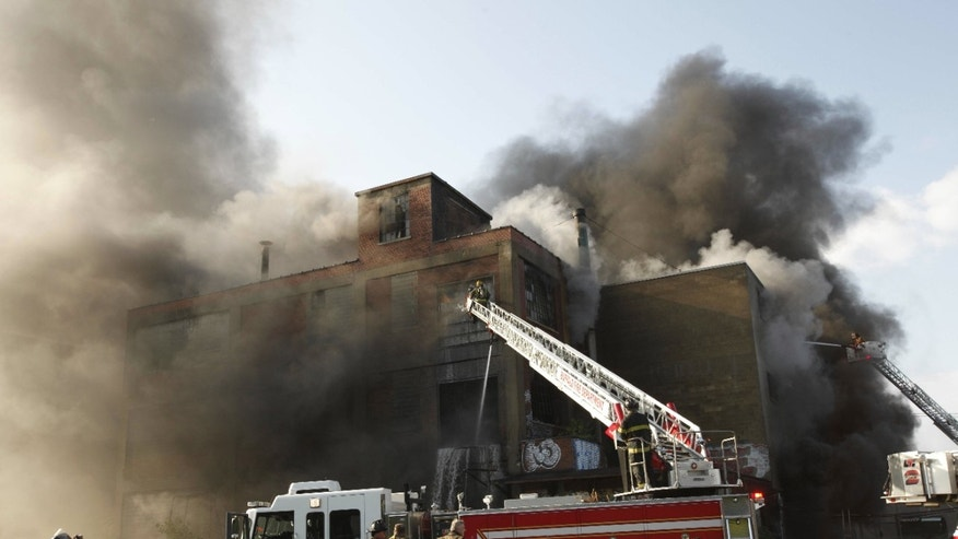 Firefighters battle a 4-alarm fire at the Niagara Lubrication complex on Chandler Street in Buffalo, N.Y. early Wednesday morning, July 13, 2011. Crews were ordered out of the building and were fighting the fire from outside the plant, which manufactures industrial lubricants.