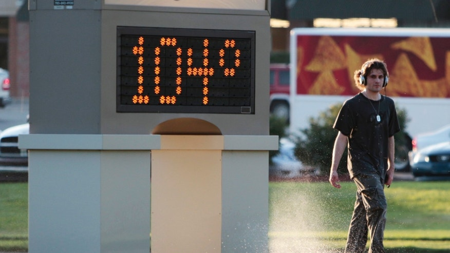 An unidentified pedestrian walks past a time and temperature sign in Lawrence, Kan., Monday, July 11, 2011. Heat advisories and excessive-heat warnings were issued Monday for 17 states in the Midwest and South.