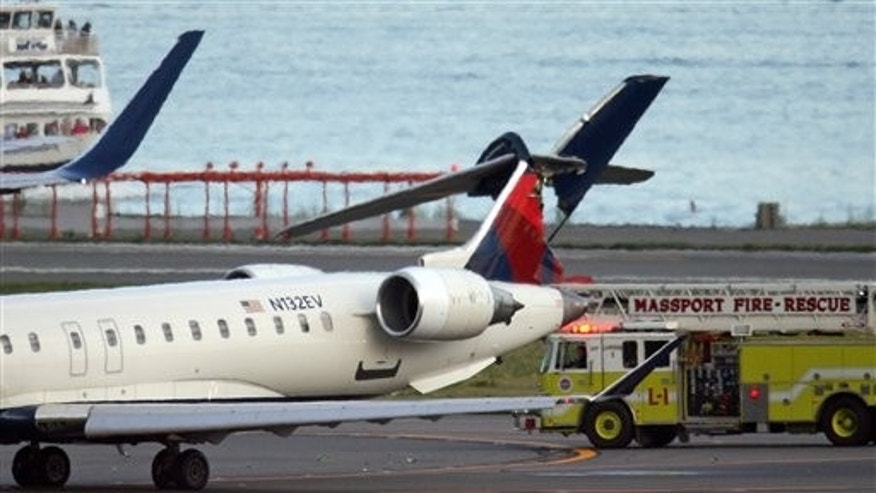 July 14: A Delta Connection jet's tail is badly damaged after it was struck by a Delta Boeing 767 airliner Thursday evening at  Boston Logan International Airport.