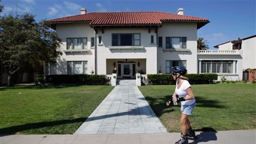 July 14: A woman passes the historic Spreckels mansion, in Coronado, Calif. A woman found dead at the historic mansion was nude and hanging from a balcony with her hands tied behind her back and her feet bound, investigators said Thursday.