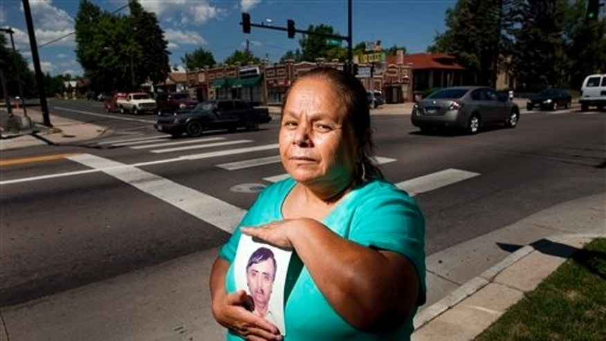 June 28: Olga Ladezma holds a picture of her husband, Lucio Ledezma, who she witnessed being struck by a car and killed nine years ago at this intersection - 44th Ave. and Federal Blvd. in Denver.