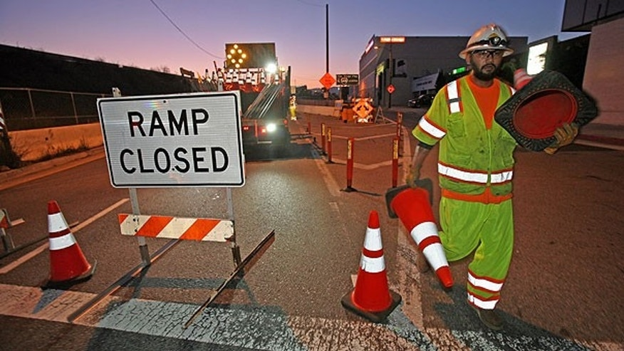 July 16: A construction worker places orange cones to close the ramp of Interstate 405 freeway at Santa Monica Boulevard in Los Angeles.