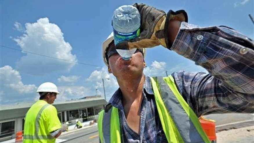 July 13: Jose Robles, foreground, crew with SD & C Inc., drinks some water as he and his colleague Jabier Garcia, left, work on decoration on Main Street in downtown Tucker, Ga.