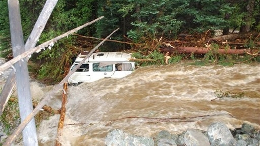 July 19: In this photo provided by Wyoming Highway Patrol, a van which was carrying four members of a family who died, is seen downstream from washed-out section of Wyoming Highway 130 in the Medicine Bow Mountains in southern Wyoming. They were fleeing torrential rains at a national forest campground.
