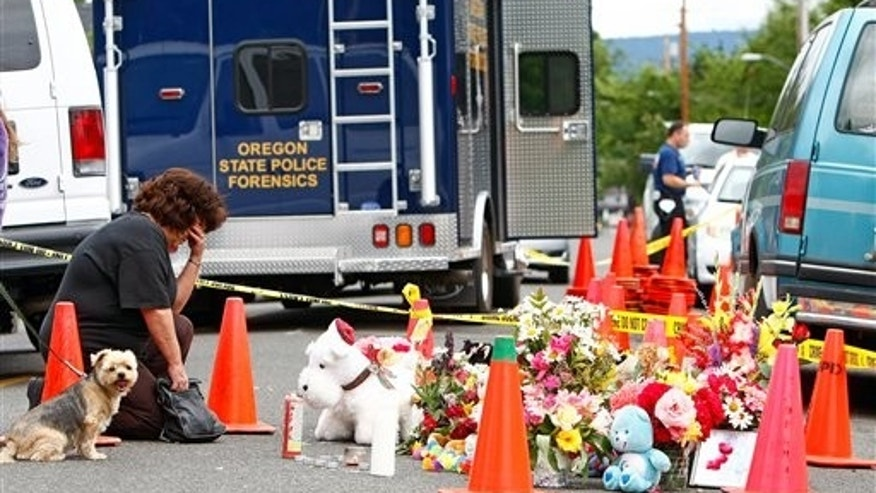July 19: Kathryn Hasha, of Medford, Ore., says a prayer at a memorial set up in front of the home where police say an Oregon man killed his wife and four children and set fire to their house on Monday, in Medford.