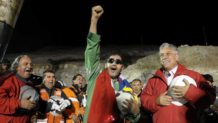 October 13, 2010: The last miner to be rescued, Luis Urzua, center, gestures as Chile's President Sebastian Pinera, right, looks on after his rescue from the collapsed San Jose gold and copper mine where he had been trapped with 32 other miners for over two months near Copiapo, Chile.