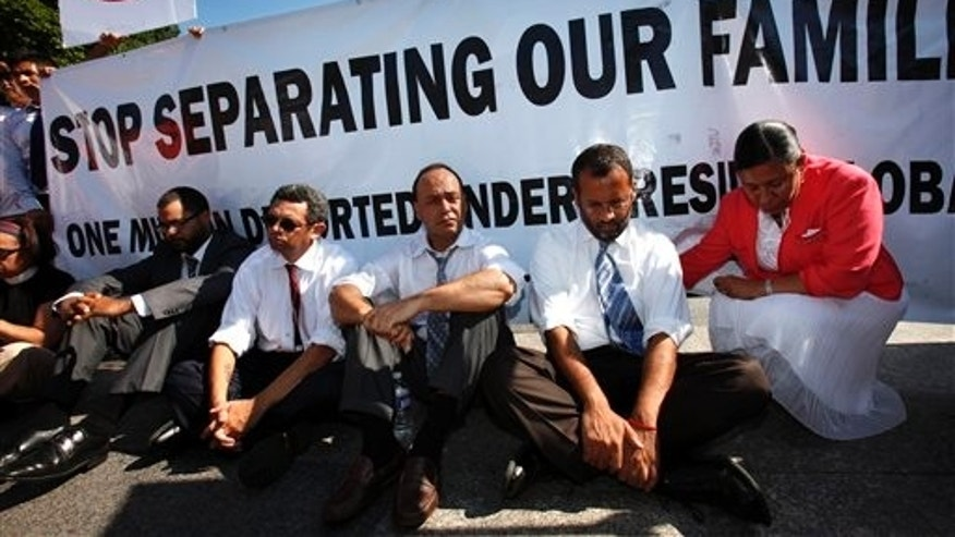 July 26: Supporters of the DREAM Act, including Rep. Luis Gutierrez, D-Ill., third from right, wait to be arrested while performing an act of civil disobedience at a rally for supporting the DREAM Act and immigration reform outside the White House in Washington, D.C.