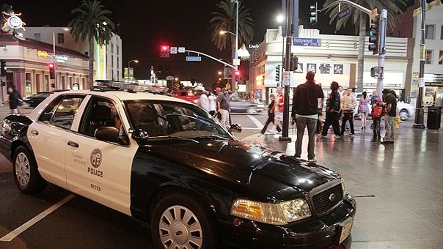 July 27: Los Angeles Police car is parked at the intersection of Hollywood Boulevard and Highland Avenue after an unruly crowd trying to attend an Electric Daisy Carnival concert film threw rocks and bottles at police cars in Los Angeles.