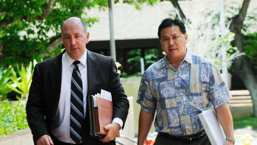 July 28: Alec Sou, right, walks toward the federal courthouse in Honolulu with his attorney, Thomas Bienert Jr. Aloun Farms owners, Alec and Mike Sou, are standing trial on federal charges that they brought 44 workers from Thailand to Hawaii and economically trapped them into working on the farm for little pay and in bad conditions.