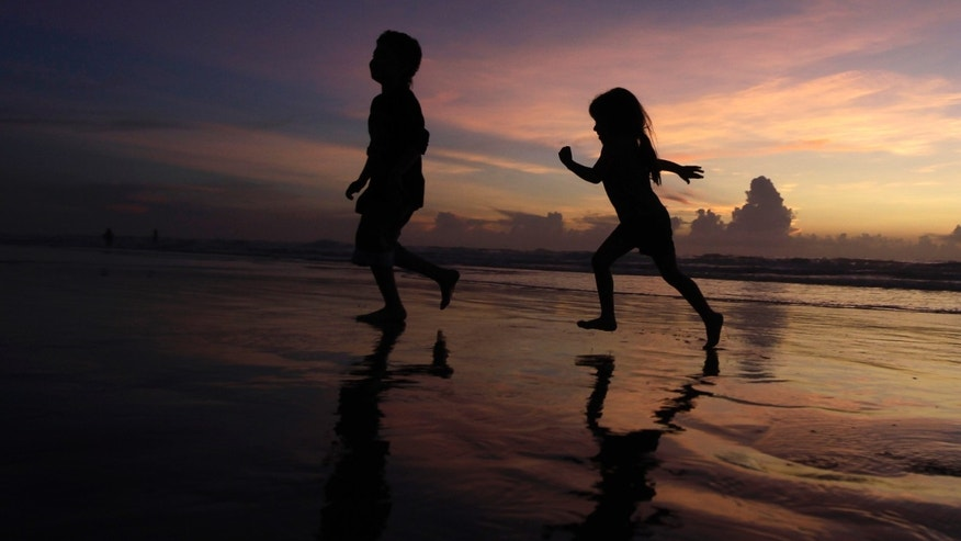 July 30: Manuel Cruz, left, 9, and his sister Lindsay, 6, run along the beach as the sun rises on South Padre Island, Texas. South Texans may awaken to some puddles, but as a rainmaker Tropical Storm Don was a dud and the tropical systems lingering showers are headed for Mexico.