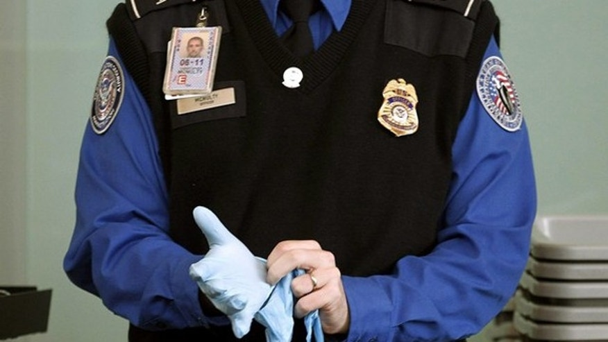 A TSA agent dons rubber gloves at a security checkpoint at Washington Reagan National Airport in Washington, November 22, 2010. U.S. authorities will reconsider airline passenger screening procedures that have caused public uproar on the eve of the busy holiday travel season, the top transport security official said on Monday.     REUTERS/Jason Reed   (UNITED STATES - Tags: POLITICS TRANSPORT CRIME LAW IMAGES OF THE DAY)