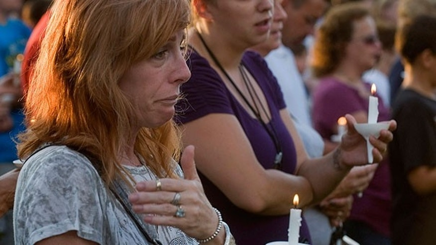 Aug. 7: Bambi Lynn of Fairlawn, Ohio, wipes away tears during a prayer vigil at Copley Community Park in Copley Township, Ohio.