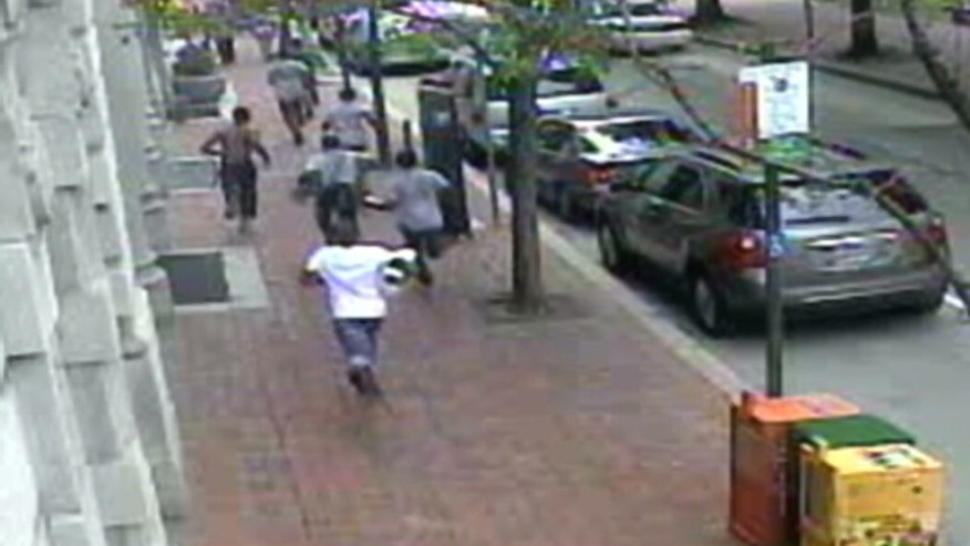 "This security image, obtained by Fox affiliate WTXF-TV, shows a group of teens running from an alleged ""flash mob"" attack in Philadelphia's Old City section on July 29. Three juveniles have so far been arrested in connection to the assault on an innocent bystander, police said."