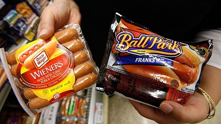 In this May 22, 2009 file photo, a store employee holds packages Oscar Meyer wieners, a Kraft product, left, and Ball Park franks, a Sara Lee Corp. product, at a local Dahl's grocery store in Des Moines, Iowa.