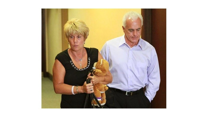 May 24: Cindy Anthony, holding a teddy bear, and her husband, George Anthony, leave the courtroom after listening to the first part of the state's opening arguments in their daughter's first-degree murder trial, at the Orange County Courthouse, in Orlando, Fla.