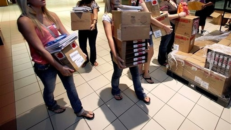 August 17: Students in a cadet teaching class carry donated school supplies to a classroom on the first day of school at a temporary high school in a converted big-box store  in Joplin, Mo.