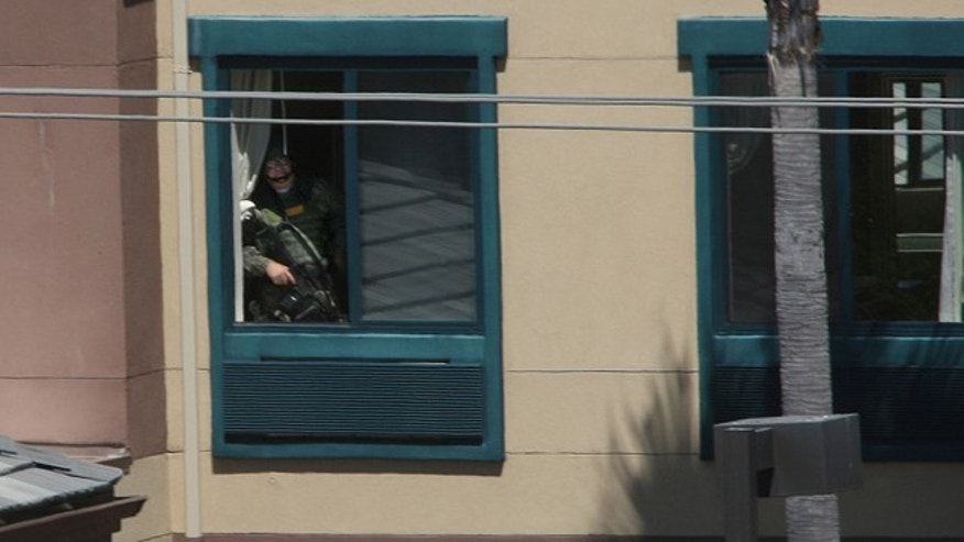 A police officer looks towards the room where an armed man had barricaded himself at an Extended Stay Hotel.