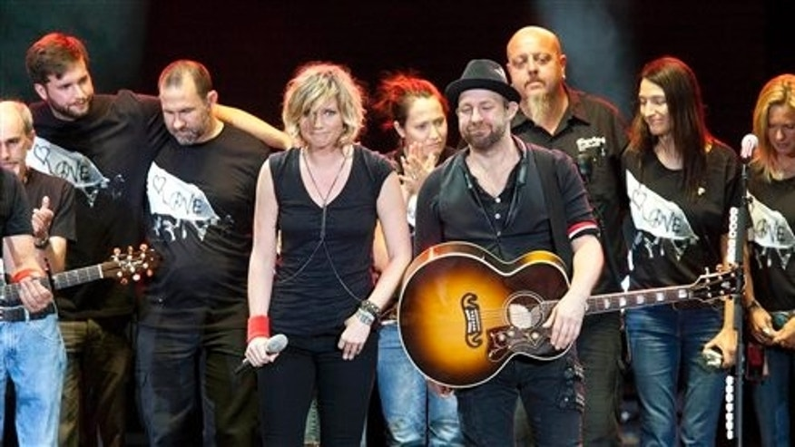 August 18: Surrounded by their tour crew, Sugarland duo Jennifer Nettles and Kristian Bush react after performing in Albuquerque, N.M. during a tribute for the victims of a stage collapse at the Indiana State Fair that killed six people.