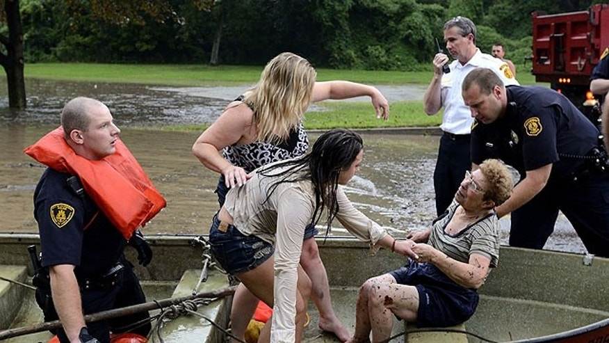 August 19: Romy Connolly is lifted from a rescue boat by Pittsburgh emergency responders after being caught in a flash flood, in Pittsburgh.