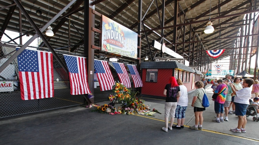 August 16: Patrons walk past a memorial in front of the Grandstand at the Indiana State Fair in Indianapolis. The memorial is set-up for those who were killed when a stage collapsed Saturday night. As the Indiana State Fair reopened, questions lingered about the structure's safety.