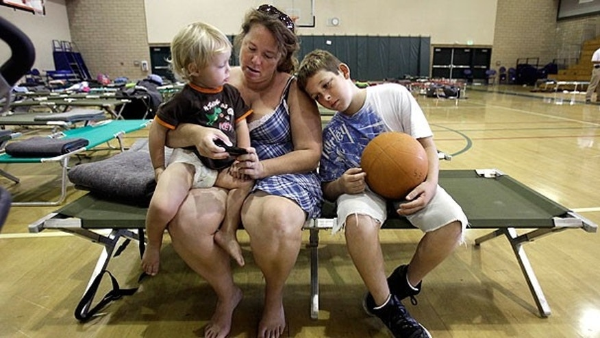 Aug. 24: Danielle Bacus checks her cell phone for messages as she waits with her sons, Izaiah Smith, 2, left, and Kaiden Bacus, 9, at an evacuation center in Lincoln, Calif.