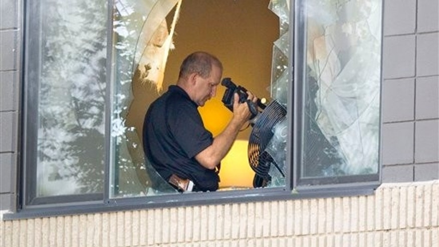 August 23: A Moscow police officer examines a video camera in a room rented by Ernesto Bustamante at the University Inn-Best Western in Moscow, Idaho.