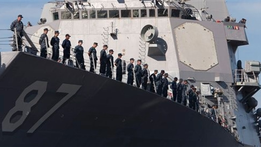 August 25: Members of the crew of the guided missile destroyer Mason man the rails as the ship pulls away from Pier 5 at the Norfolk Naval Station ahead of approaching Hurricane Irene.