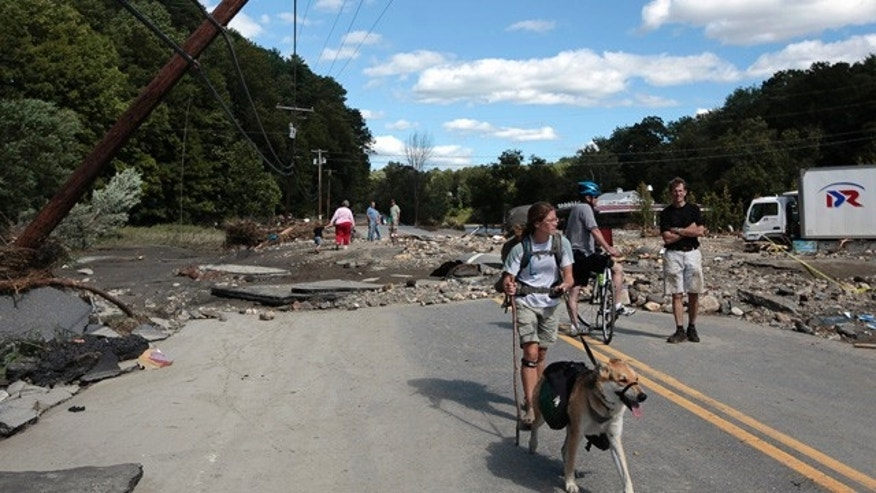 Aug. 29: Lindsey Jones makes her way down floodwater-damaged Rte. 4 in Woodstock, Vt.