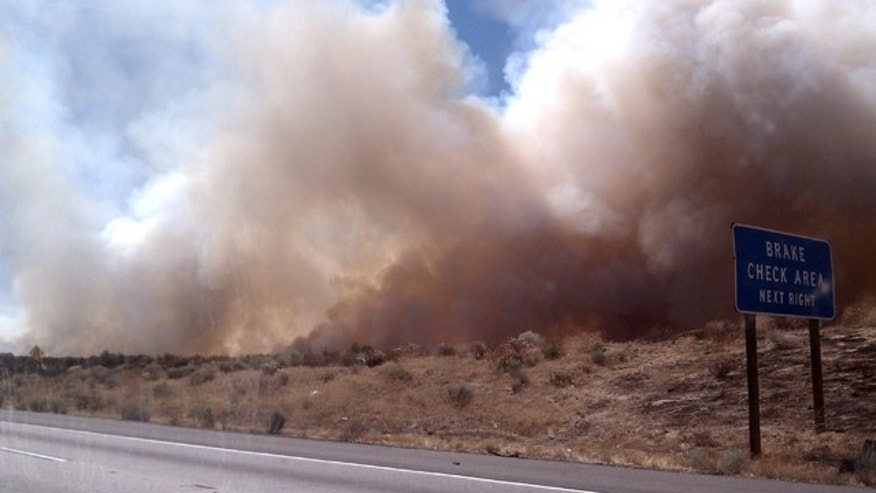 This image provided by Cindy Kent shows a wildfire burning alongside Interstate 15, Friday Sept. 2, 2011in the high desert northeast of Los Angeles. This wildfire burning in Southern California national forest land has partially shut down the major freeway between Los Angeles and Las Vegas.