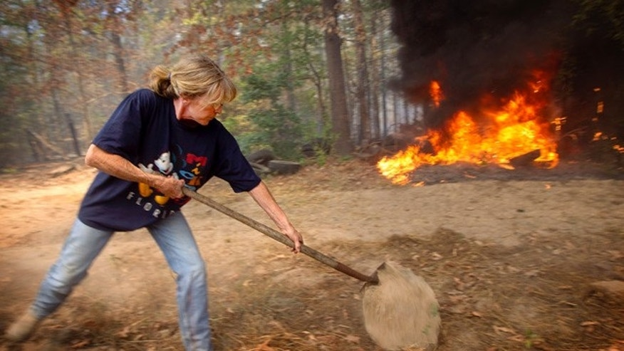 Sept. 6: Tammy Heath spreads dirt on the smoldering ground in an attempt to keep a fire from jumping a fire break in Linden, Texas.