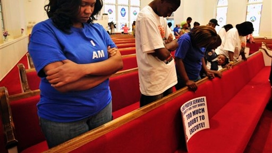 September 17: Troy Davis' youngest sister Ebony Davis prays along with some of her family members during a prayer vigil at the St. Philip Monumental AME Church in Savannah, Ga.