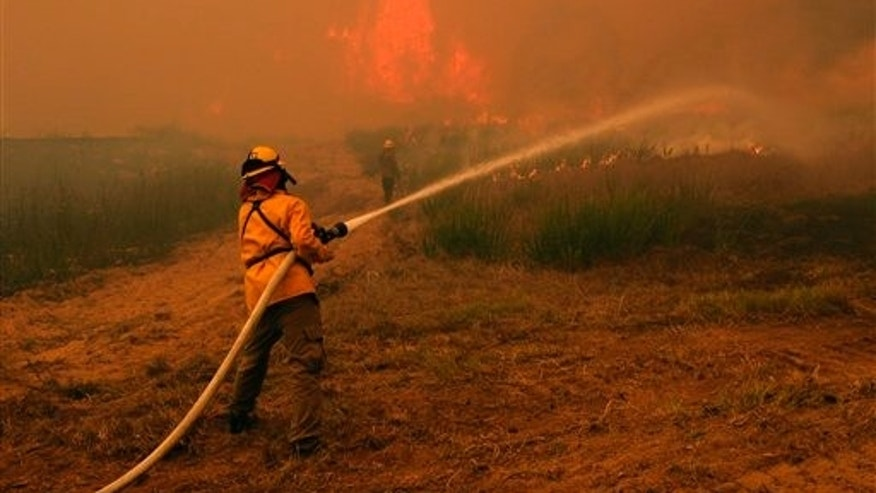 In this Sept. 5, 2011 file photo, firefighters battle a large wildfire near Smithville, Texas