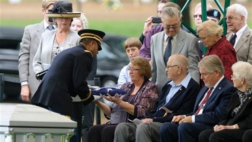 September 21: Bonnie Williams, daughter of Tech Sgt. Robert L. Christopherson, receives a flag from Army Chaplain John Gabriel during a during a burial ceremony for nine WW II Army Airmen at Arlington National Cemetery in Arlington, Va.
