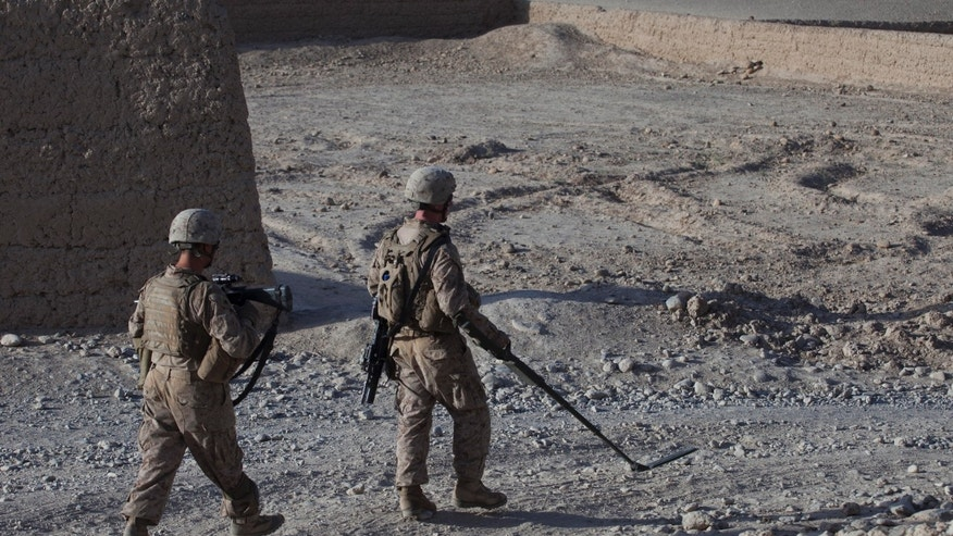 September 5: U.S. Marines patrol with the help of a metal detector, in Sangin district, Helmand province. Sangin has one of the highest concentrations of improvised explosive devices in the country, resulting in high numbers of Marine infantrymen losing limbs and vital organs.