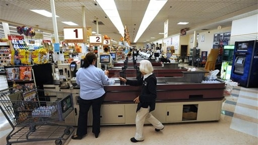 In this Sept. 23, 2011 photo, cashier Joyce Mackie, right, comes to the aid of a customer having a problem at a self-serve checkout station at a Big Y supermarket in Manchester, Conn.