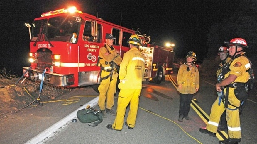Sept. 29: Los Angeles County firefighters are stationed on Lake Hughes Road, where two vehicles were found off the side and approximately 200 feet in the canyon below in the Angeles National Forest, north of Castaic, Calif.
