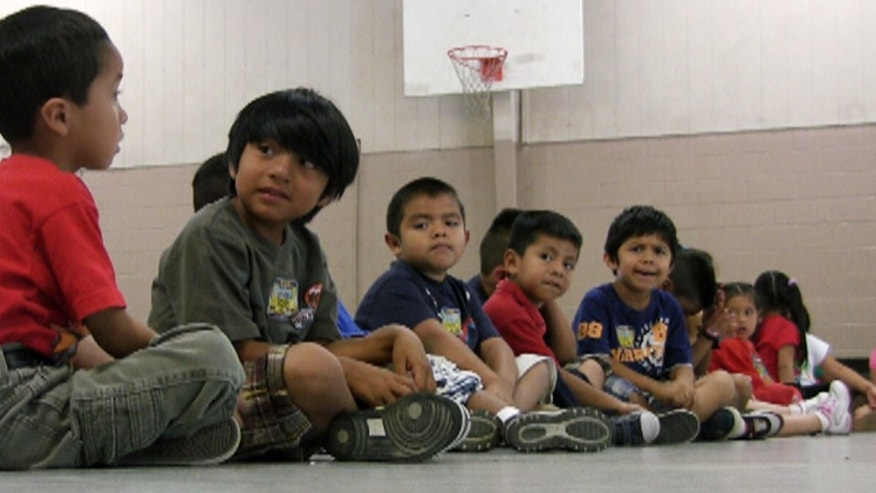 FILE - In this Aug. 17, 2011 file photo, students sit in the gym at Crossville Elmentary School in Crossville, Ala. Despite being in an almost all-white town, the school's enrollment is about 65 percent Hispanic. Hispanic students have started vanishing from Alabama public schools in the wake of a court ruling that upheld the state's tough new law cracking down on illegal immigration. Education officials say scores of immigrant families have withdrawn their children from classes or kept them home this week, afraid that sending the kids to school would draw attention from authorities. There are no precise statewide numbers. But several districts with large immigrant enrollments — from small towns to large urban districts — reported a sudden exodus of children of Hispanic parents, some of whom told officials they would leave the state to avoid trouble with the law, which requires schools to check students' immigration status. (AP Photo/Jay Reeves, File)